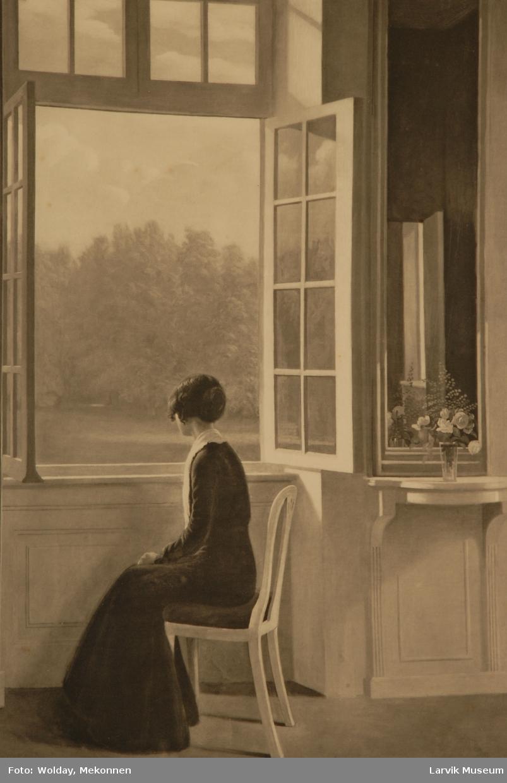kvinne som sitter på en stol og ser ut av vindu