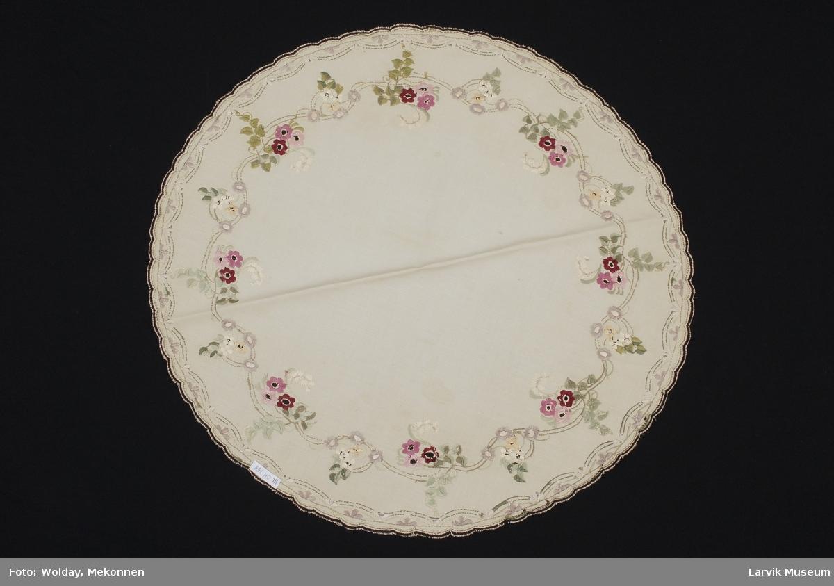 Form: Sirkel formet, tunger rundt kanten, Brodert med blomster i kanten.