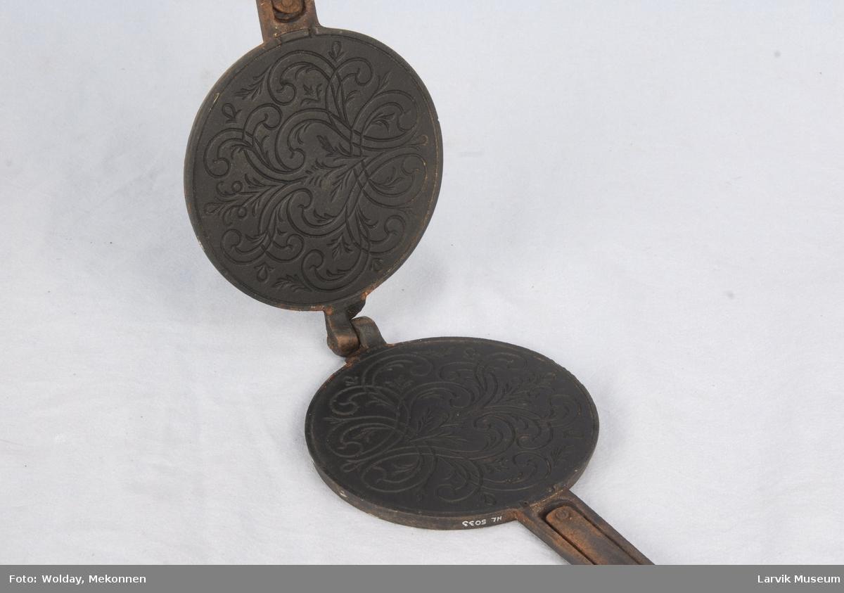 Form: To sirkelformede deler som er festet til to lange håndtak og hengslet sammen i den andre siden. De to platene er dekorert med mønster inni slik at kakene får mønster. Kromkakejern til å legge på varm plate.