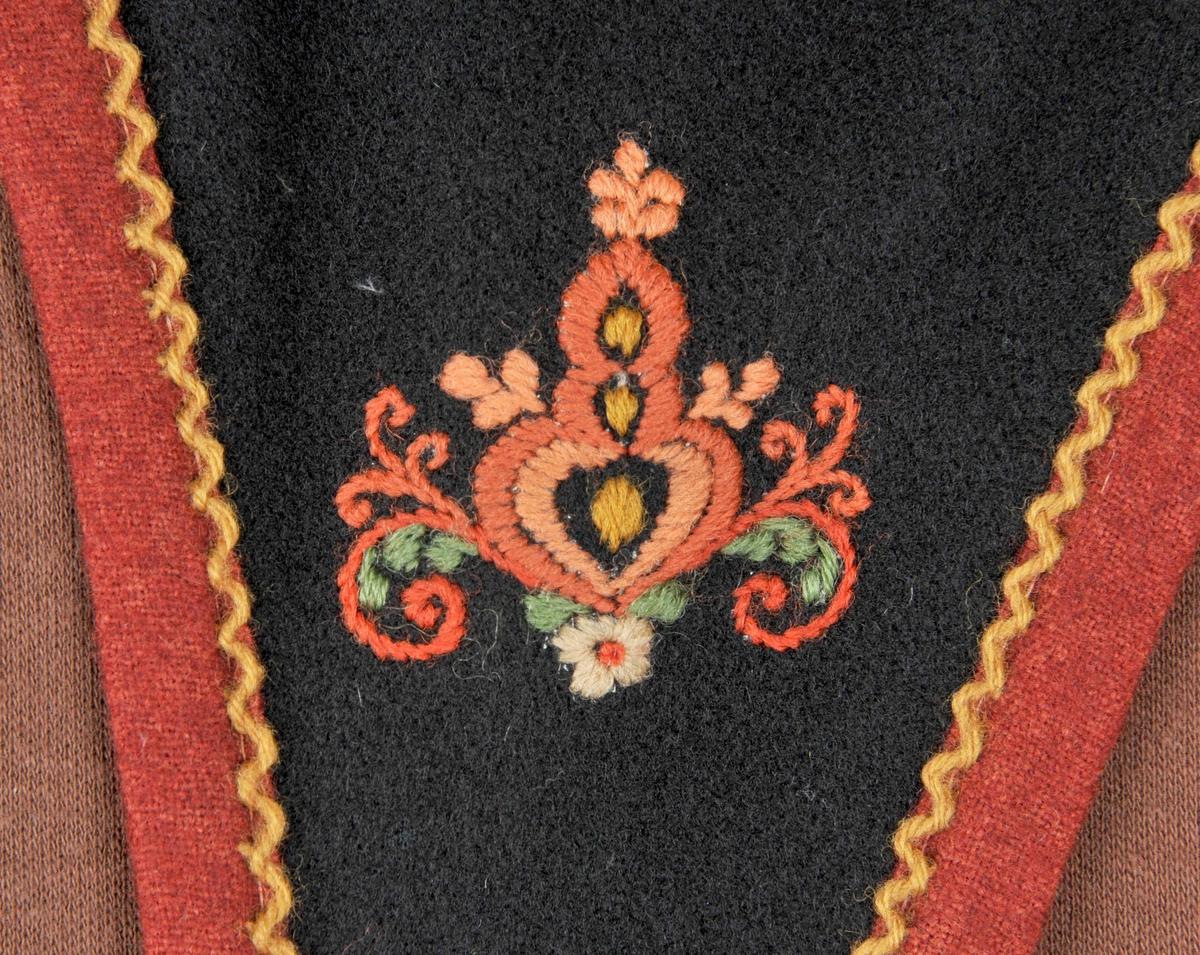 Stakk, liv, forkle og trøye av svart ullstoff, kanta med rustraudt. Alle delar har rosesaum.