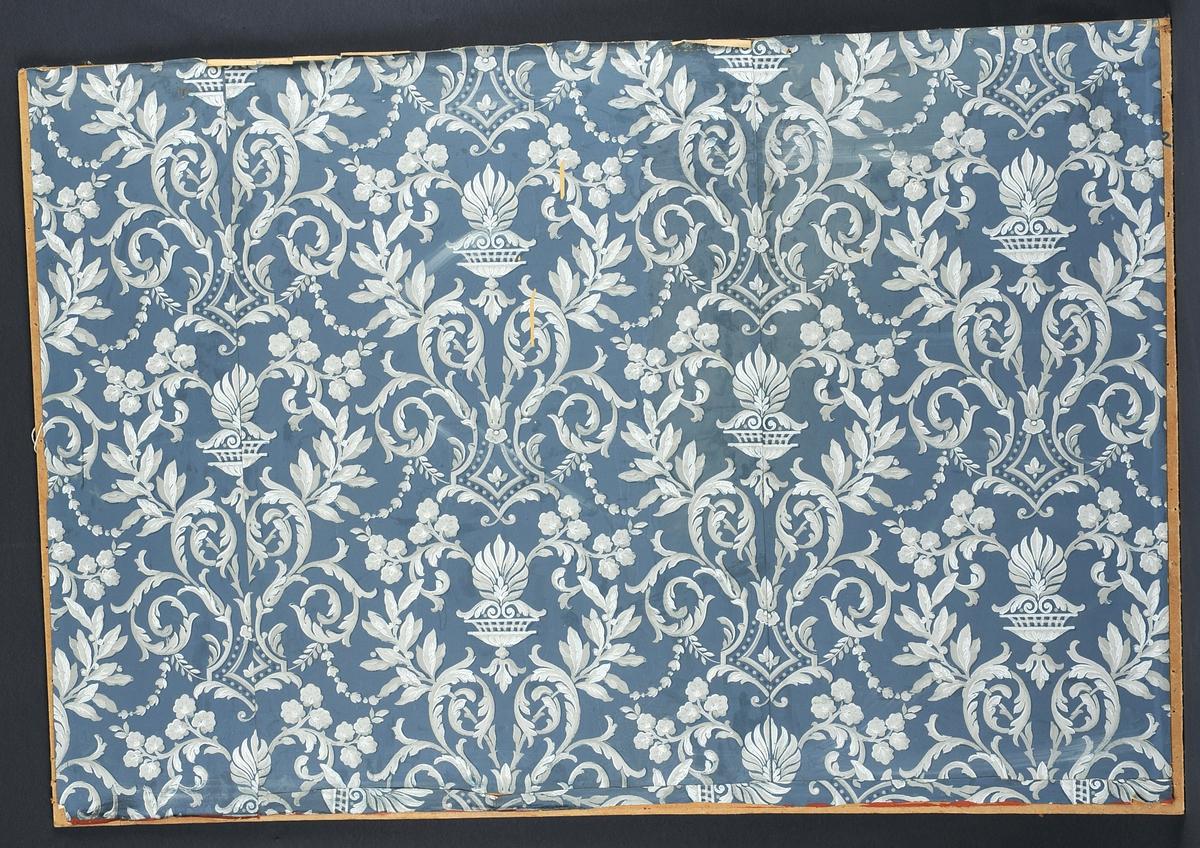 Tapet, blå botn med kvit dekor i akantus og liljeform. Fest på plate av huntonitt. Frå hytta til Henrik Sørensen i Smørklepp i Vinje.