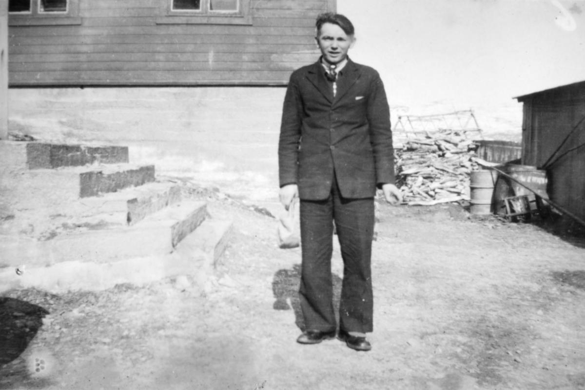 En ung, dresskledt mann poserer utenfor et hus. Sted og person er ukjent, men bildet kan være tatt i Kvalsund kommune.