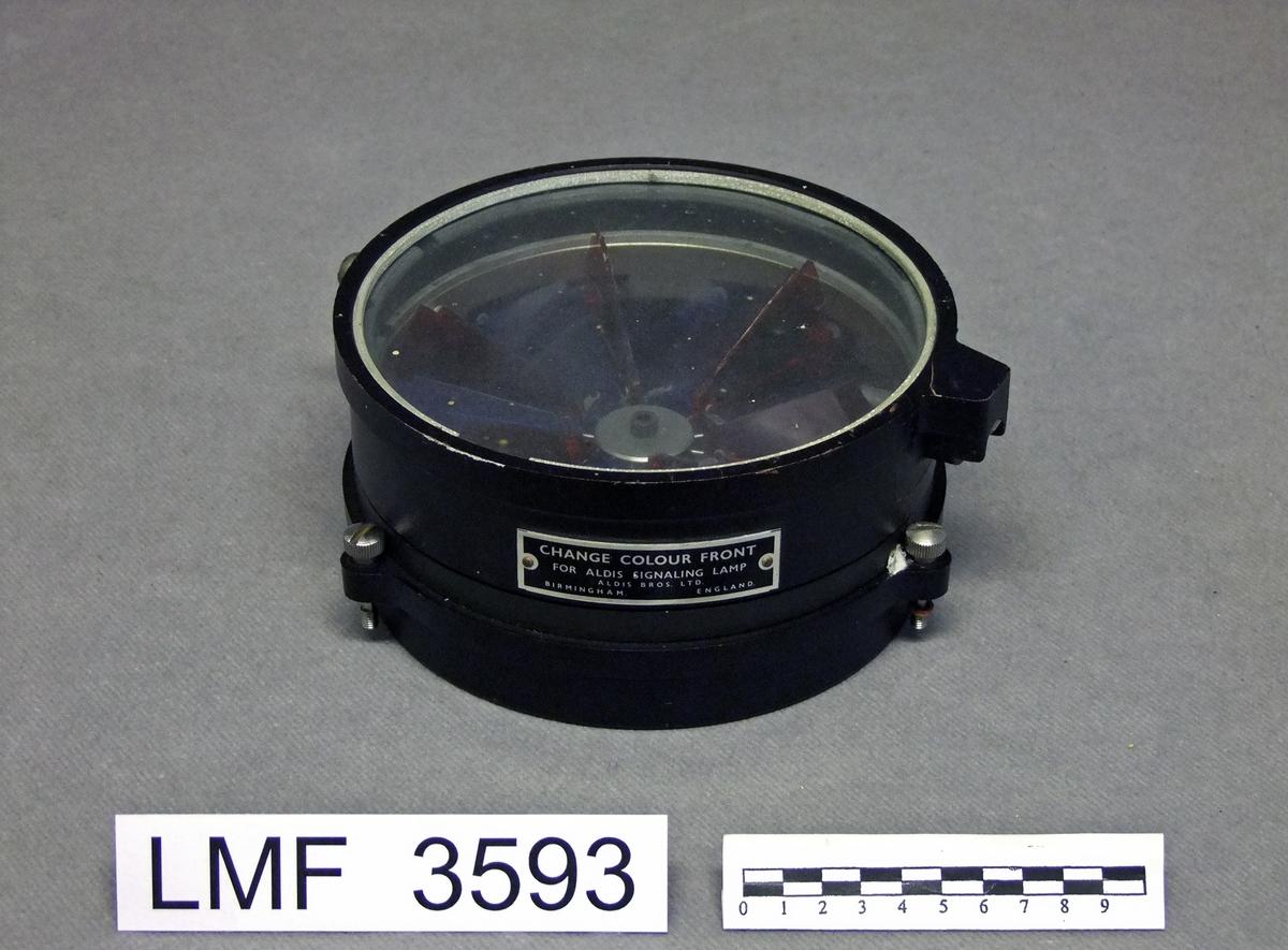 Fargeveksler med tilhørende kasse. Brukt ifm. morse-signalering mellom to skip. Fargeveksleren ble montert foran på en ALDIS-signallampe for å kunne veksle mellom rødt eller blått lys.  Form:  sirkulær, kassa kvadratisk