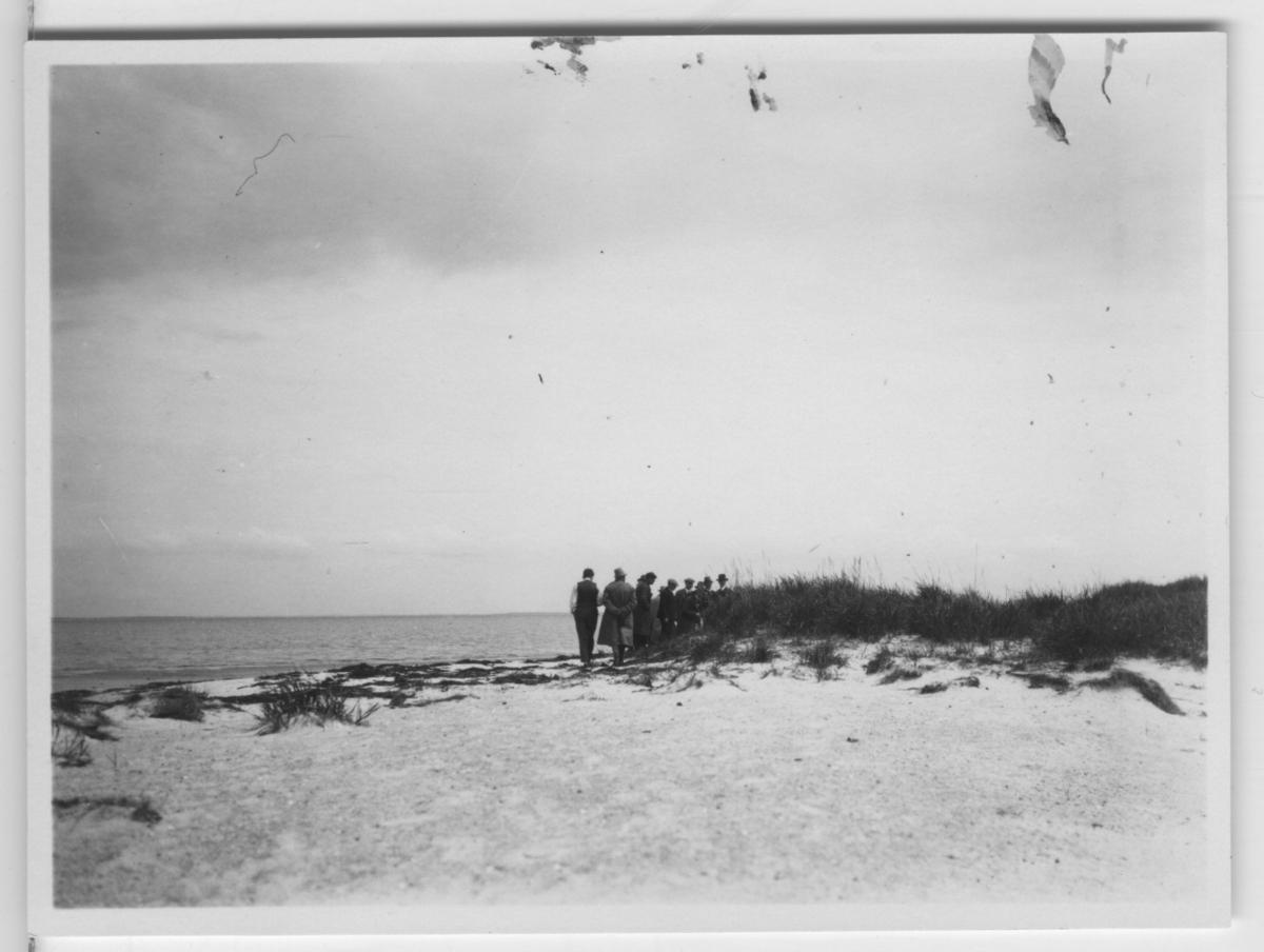 'Göteborgs Biologiska förenings utfärd till Måkläppen och Falsterborev: ::  :: Ca 10 män stående i grupp på stranden, vy ut mot havet. ::  :: Se fotonr. 1384-1395, 1618-1639, 1640-1648 samt 3229 från samma utfärd.'