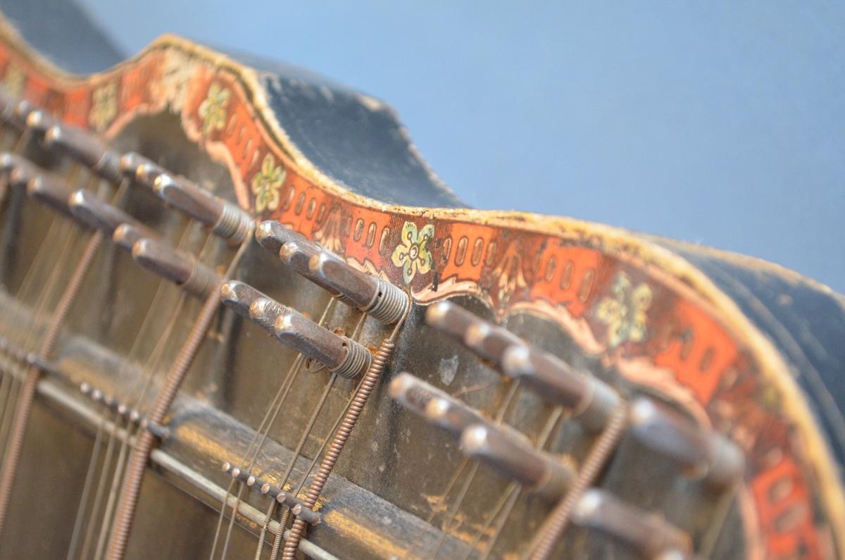 """Motiv 1: Harpespillende valkyrie sittende på jordklode, omkranset av laubergkrans, i fargene bronse, blått og rødt.   Motiv 2: Blad- og blomsterornament, symetrisk plassert rundt harpens lydhull, i fargene bronse, blått og rødt.  Motiv 3: """"Stemmeinstruks"""" omrammet av laurbærkrans i fargene blått, bronse, rødt og svart."""