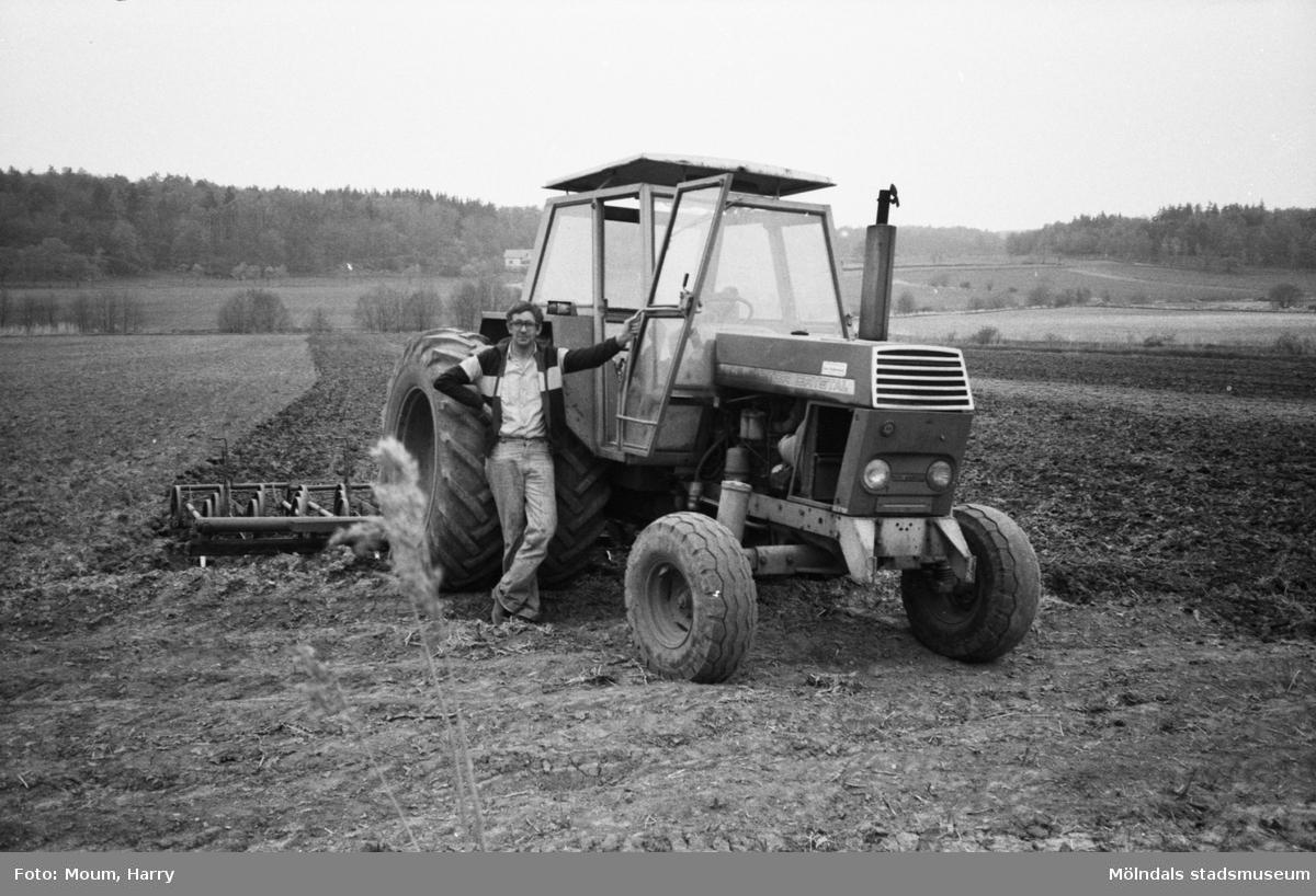"""Vårbruk i Lindome, år 1983. """"Bertil Åkesson har bråda dagar med sin traktor i vårbruket.""""  För mer information om bilden se under tilläggsinformation."""