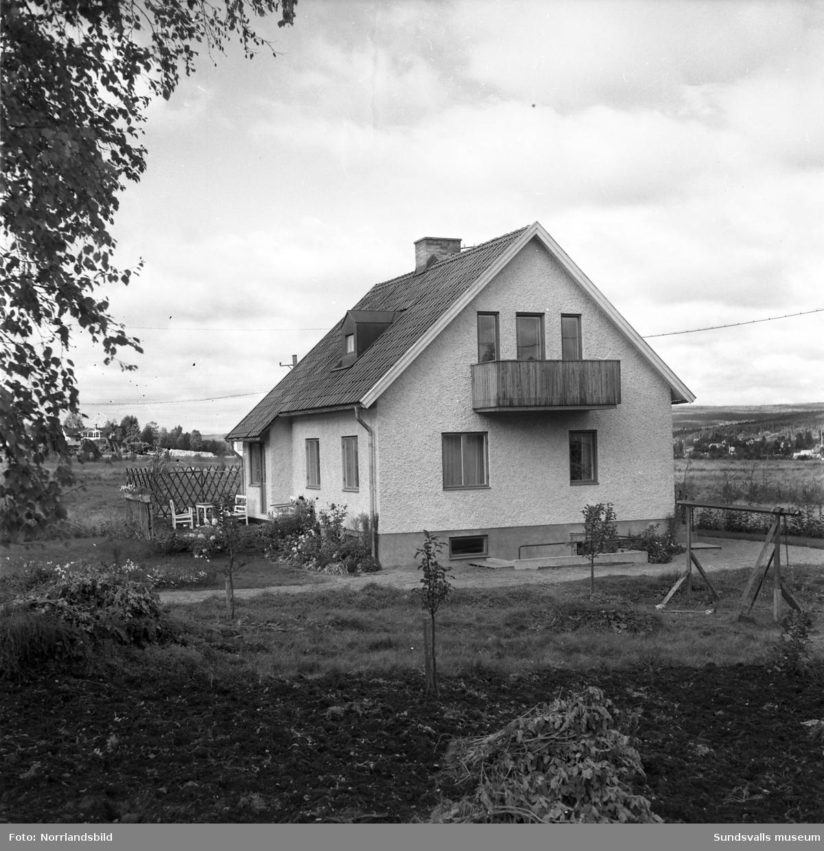 Oidentifierade byggnader: villor, flerfamiljshus, affärsfastigheter. SMC Snabbköp, EK (EIK?) Kläder Textil.