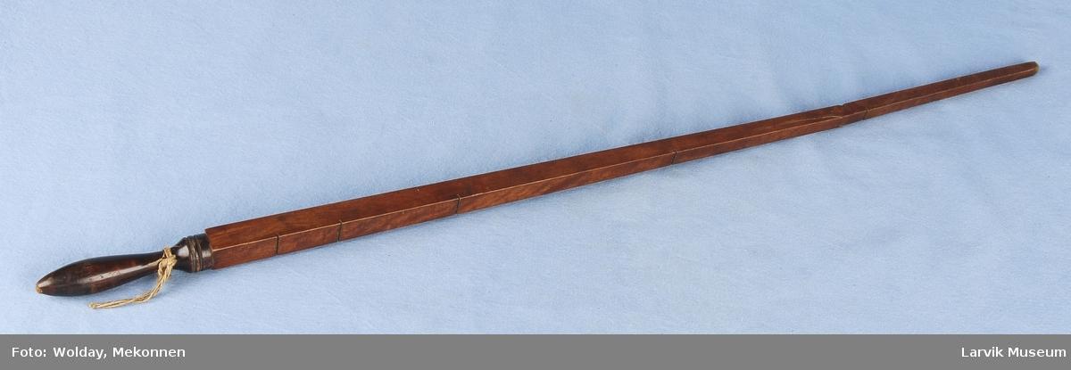 Form: Lang rettkantet stav som vider seg utovet og ender i et dreid håndtak. 5 målemerker på.