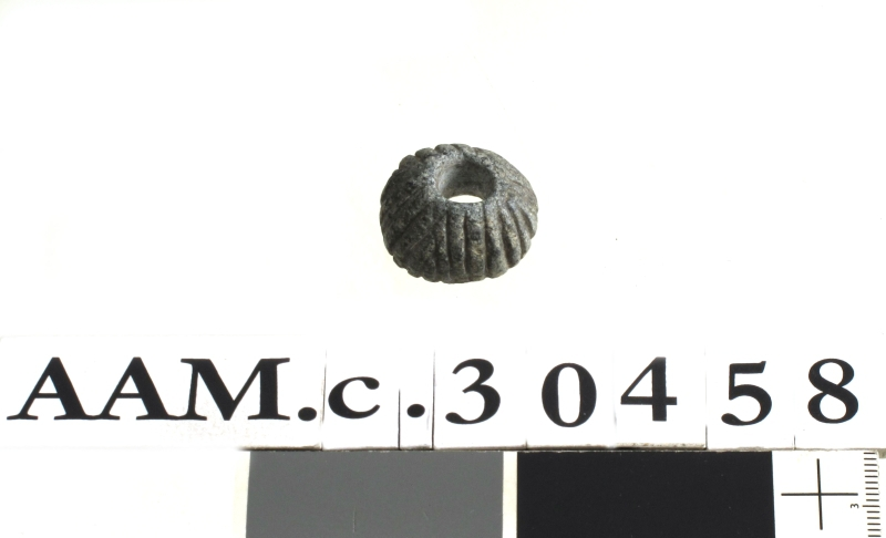 Spinnehjul av grå kleber, nærmest som Jan Petersen: Redskaper, fig. 165, men mindre og ornert med vertikale, dyptskårne linjer.