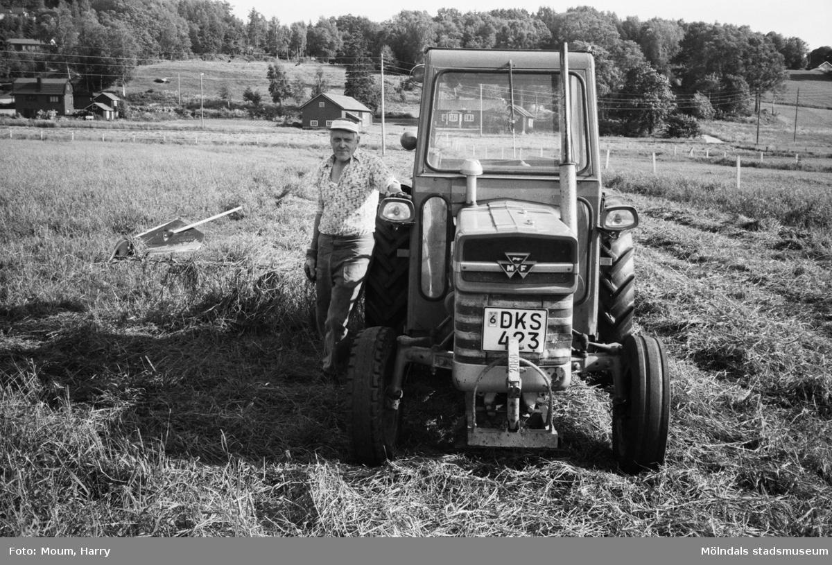 """Olle Svensson i Lindome vid sin traktor, år 1983. """"Slåttern är i full gång. Olle Svensson tar en paus i körningen.""""  För mer information om bilden se under tilläggsinformation."""