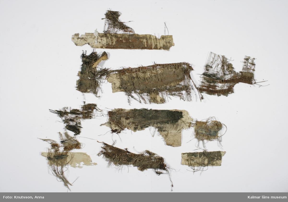 KLM 43826. Tapet, vävd fransk tapet. 21 st bitar. Varp av lingarn och tråd av ylle. Tapeten är en så kallad fransk tapet. Mönstret är i zick-zack med mörkblå, grön och orange färg. Tapeten är vänd på och en pappskiva är uppklistrad på baksidan. Pappskivan är målad med färg i gräddvitt. Vissa delar av baksidan har varit tapetserade i en mörk 1890-talstapet med blommor på. Datering: Slutet av 1600-talet.