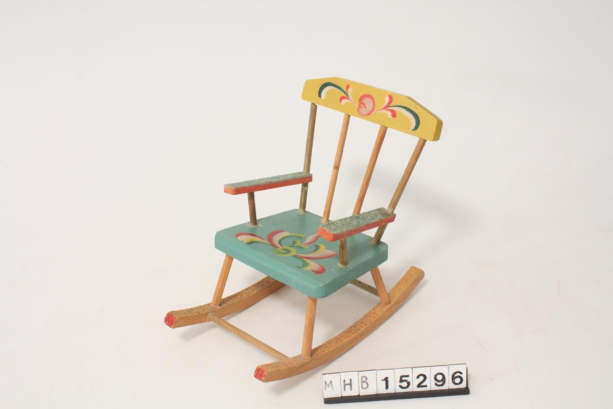 Det er malt dekor på setet og stolryggen, dekoren er inspirert av rosemaling.
