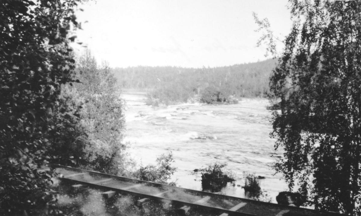 """""""Mennika-foss i Pasvig.""""  Vi ser fossen med skogen i bakgrunnen og jernbaneskinnen til A/S Syd-Varanger i forgrunnen."""
