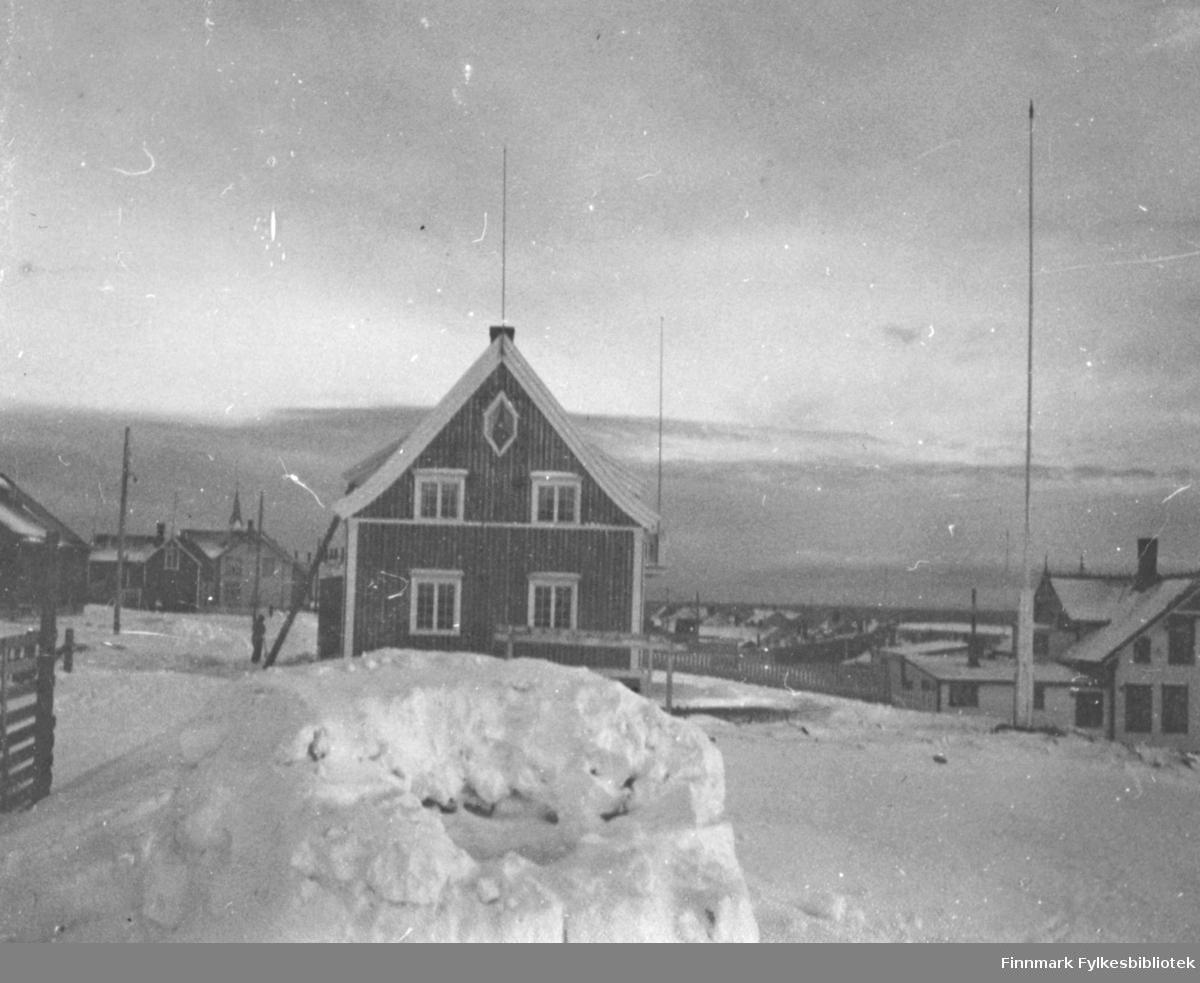 Et vinterbilde fra Damsveien i Vadsø. Huset midt i bildet tilhørte Harald Hofseth. Den store bygningen til høyre i bildet er Esbensens sveitservilla. Begge disse husene overlevde 2. verdenskrig, selv om Hofseths hus ble bombeskadet. Foran i bildet en snehule