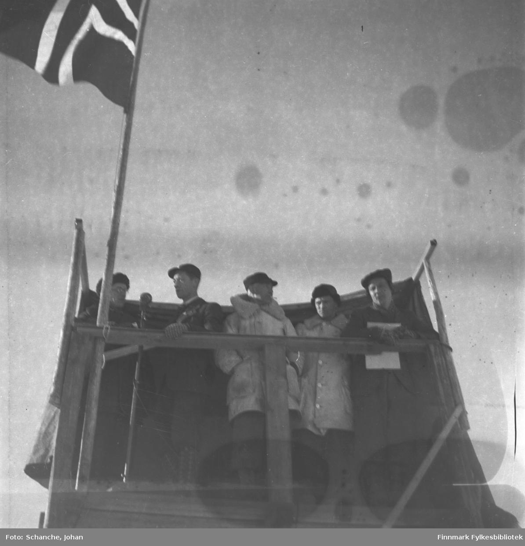 Kretsrennet på ski , Vadsø 1946. Fra dommertribunen undet hopp- rennet. Til høyre de tre dommerne Bruun, Rønbeck og B.Marki. Til venstre intervjuer hallomannen Melsvik (ytterst) truppleder Nordli over Finnmark Kringkaster.
