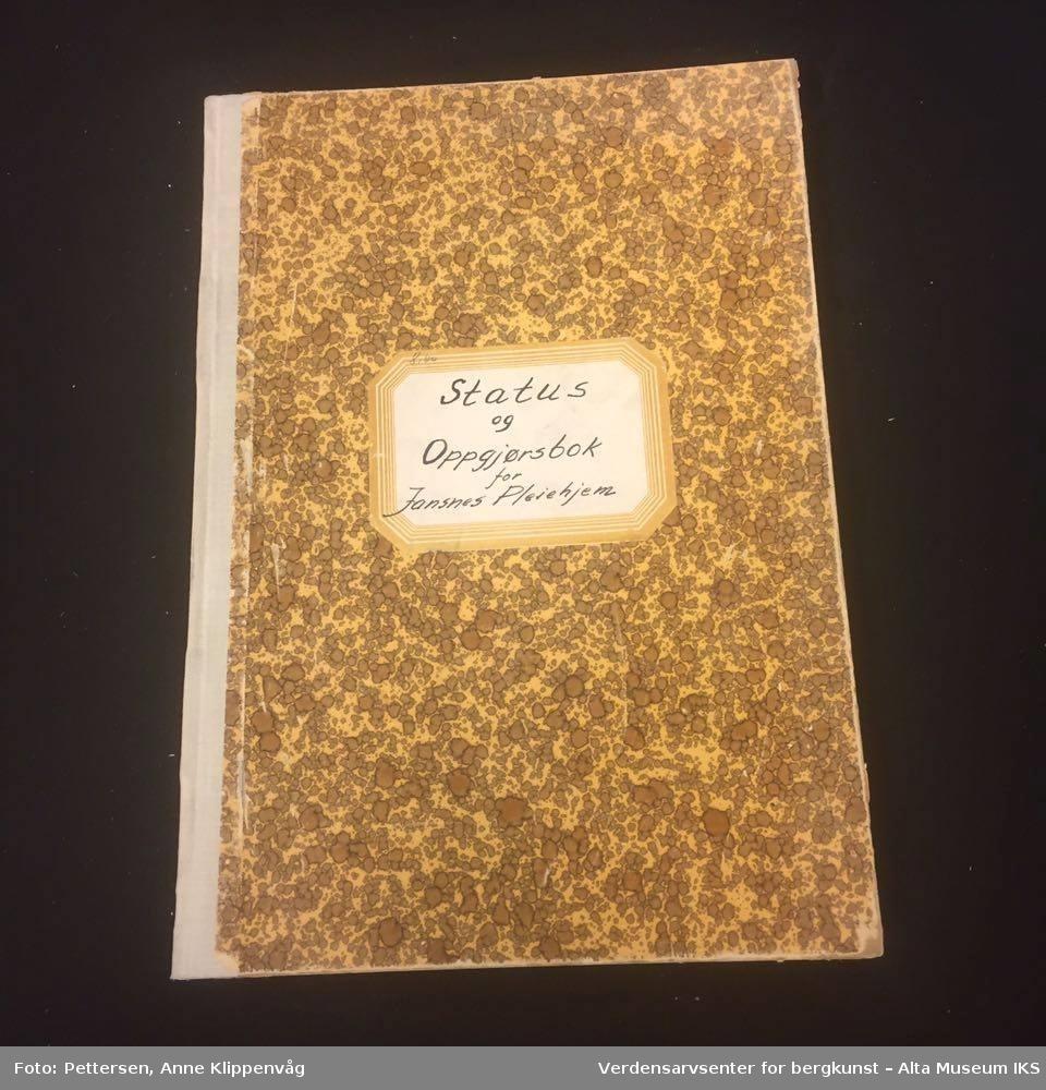 Rektangulær notatbok, innbundet med harde permer. Brunmønstret på forsiden og baksiden.