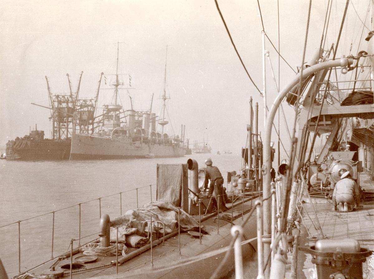 Till vänster i bilden ser vi Temperley Patent förankarad i Portsmouth hamn, med en brittisk kryssare av Eclipse klassen förtöjd längs sidan. Ubåten Hvalen låg i Portsmouth meddan den 9-19 september 1909.