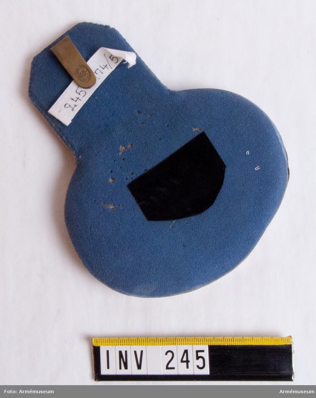 Epålett med matta i orangegult kläde (samma som vapenrockens krage). Foder i blått kläde (samma färg som vapenrocken). Plåt kring nedre delen av försilvrad metall. VIII i förgylld metall, diameter 25 mm, av dragonernas modell. Kupad, slät. På fodersidan en hake för fastsättning i vapenrocken, 35 mm lång och 10 mm bred. Ingraverat: Militärekiperingsaktiebolaget, MEA. Stoppning av halm.