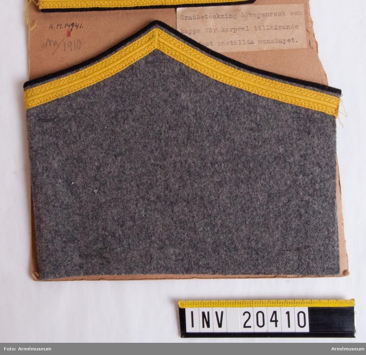 Grupp C I. Med gradbeteckning för korpral tillhörande fast anställt manskap. För vapenrock och kappa.