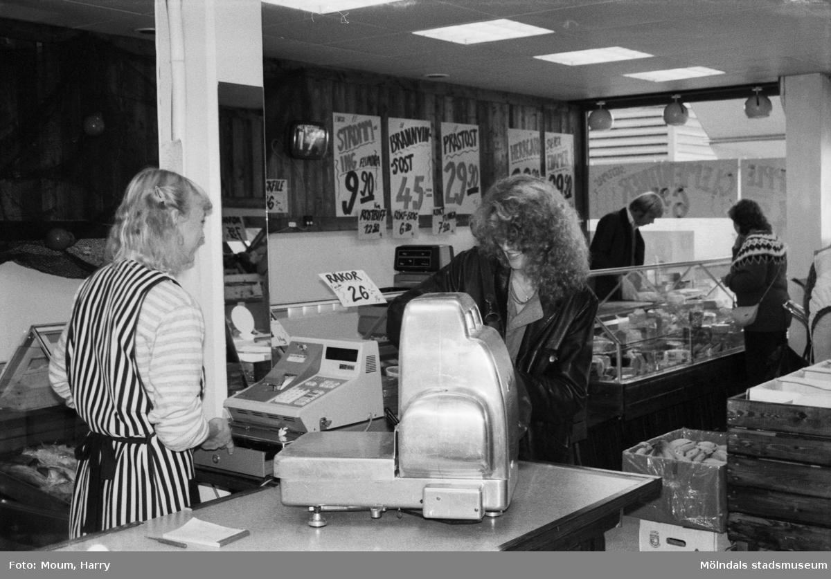 Ny fiskaffär, Fiskhörnan, på Hagabäcksleden i Kållereds centrum, år 1983. Christina Sjöbring betjänar kund.  För mer information om bilden se under tilläggsinformation.