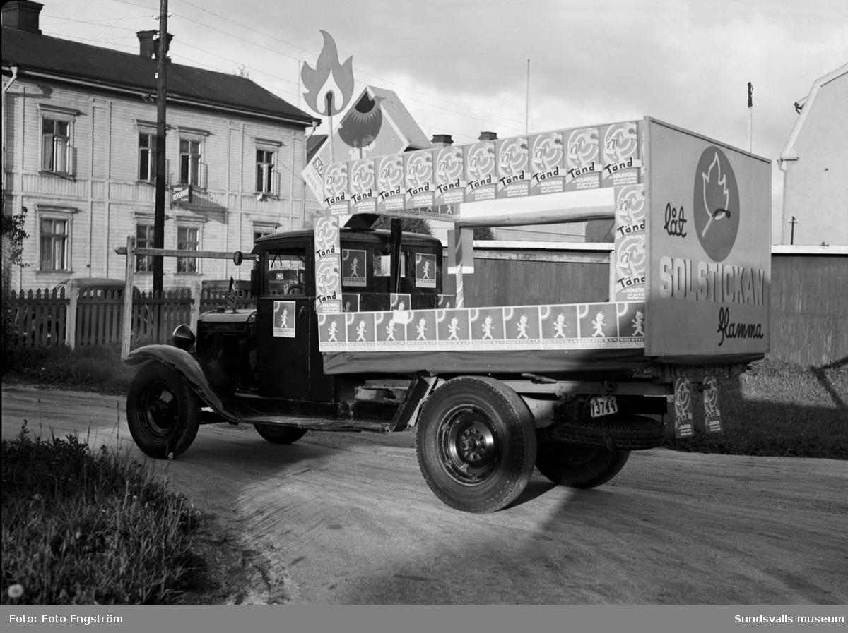Lastbild med reklam för Solstickan. Barnens Dag. Fotot är taget vid Långgatan 4. Huset vid lastbilen är Järnvägspensionatet.