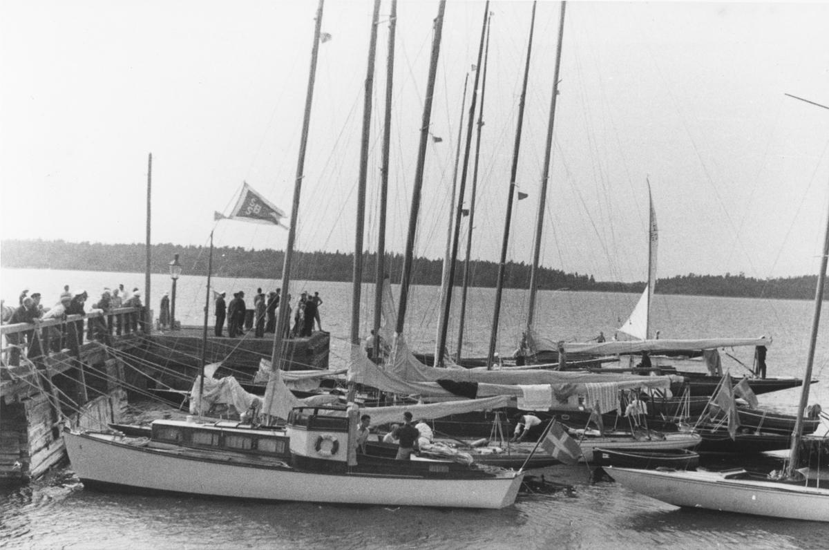 """Övrigt: Till NJK:s 75-årsjubileum 1936 begav sig en eskader från KSSS i juli till Helsingfors (""""Sjötåget""""). Ett av etappmålen för eskadern var Degerby på Föglö i Ålands skärgård, där denna bild tagits. Om Sjötåget, se KSSS årsbok 1937 s 126 ff samt Till Rors årg. II (1936) nr 6 s 8 ff."""