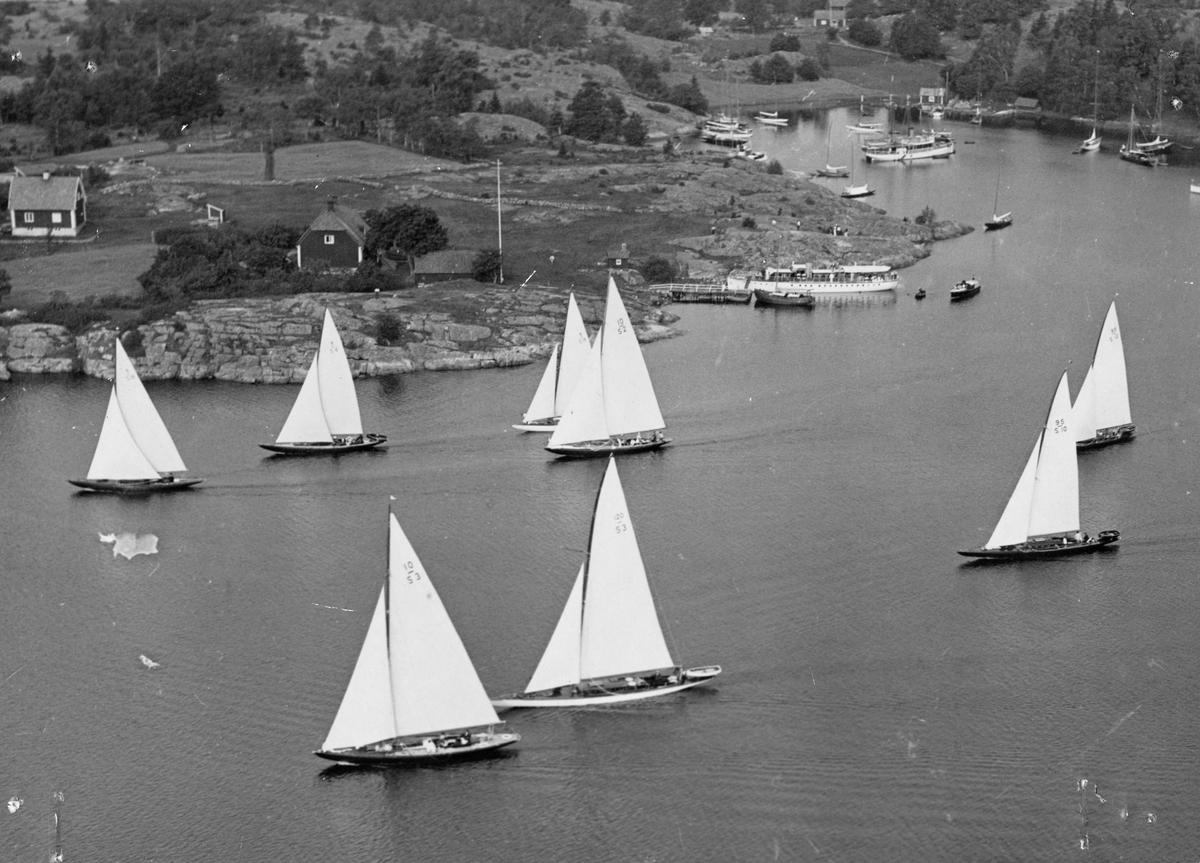 """Övrigt: Från KSSS Visbysegling 1933, som detta år utgick 28 juli från Barösund nära Valdemarsvik. Båtarna är fr v t h i bakre raden 8-S18 LAILA (b. 1928, konstr. Johan Anker), 8-S6 ERGEKÅ (b. 1930, konstr. Gustaf Estlander), 8-S19 RANJA (skymd; b. 1923, konstr. Johan Anker) samt 10-S2 REFANUT (b. 1927, konstr. Charles E. Nicholson); i den främre raden ses fr v t h 10-S3 AAVORYN (b. 1923, konstr. Sophus Weber), 120-S3 INGUN (b. 1920, konstr. Zake Westin), 95-S10 ROXANE III (b. 1922, konstr. Gustaf Estlander) samt 95-S12 AITANGA (skymd; b. 1920, konstr. Gustaf Estlander). Förtöjd närmast i h bildfält ses Erik Åkerlunds motorjakt STELLA MARINA (b. 1927, konstr. C. G. Pettersson); i viken i ö h bildfält ses ångaren BRAGE (ex BRAGE, PRINS CARL, KURRE; b. 1872, Lindholmens Verkstad). Dupletter i KSSS-samlingen Fo134125 och Fo134129. Av Fo134125 framkommer att bilden tagits från Stockholms-Tidningens reportageflygplan (""""Vikingfoto"""")."""