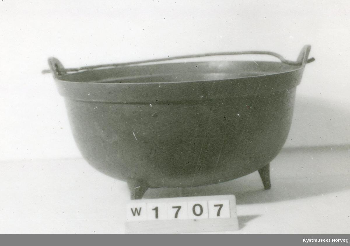 """Jerngryte brukt til å koke mat i. Gryten står på 3 bein. Har en tynn hank at stålstreng, ikke orginal. 1,7 cm. under kanten på innsiden er en 0,5 cm. bred """"Hylle"""" til lokk."""