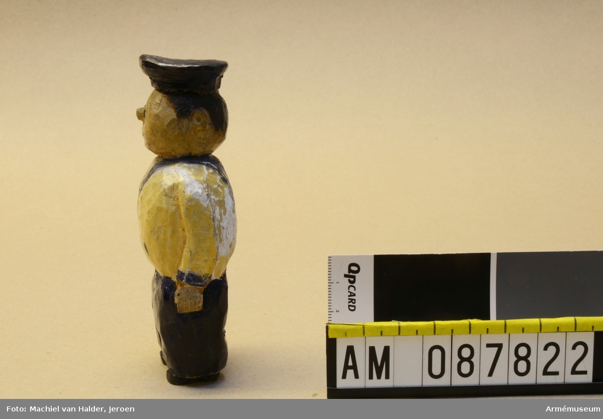 """Målad träfigur föreställande en soldat iklädd sjömansuniform. Texten """"ATOM"""" på figurens mage ska enligt givaren utläsas """"Alla Talar Om Muck""""."""