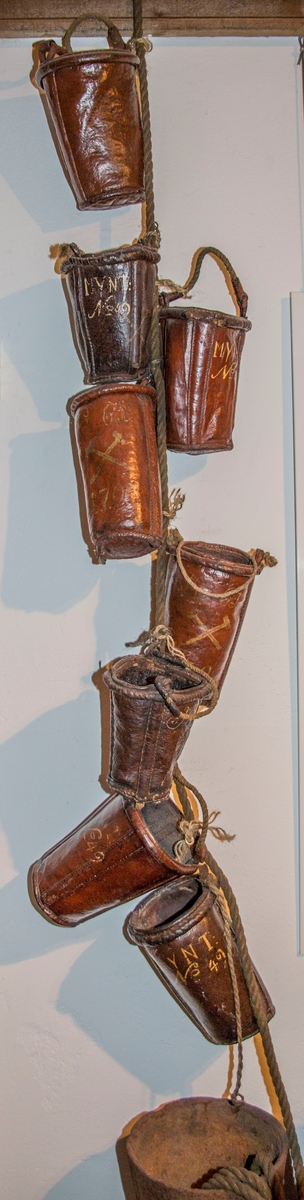 Brannbøttene er laget av fire lærdeler som er sammenføyet med søm. Det er sydd inn to tre-spiler, som går fra kanten av bøtteåpningen og og ned til bunnen. Disse er plassert vis-a-vis hverandre i forhold til bøttens diameter. Trespilene fungerer antagelig som forsterkning både av bøtten og hankefestet. Bøttene er malt med rødbrun farge både utenpå, inni, og i bunnen. Overflateundersøkelse med mikroskop viser et tynt malingslag. Malingen har trengt inn i porene i læret. Bøttene er påført nummer, eierbetegnelse og årstall med gulhvit maling. Alle malingslag fester godt til underlaget. Læret er stivt og hardt. Bøttene har vært innsatt med bekk innvendig for at de skulle være vanntette og det finnes enda rester av bekk på noen av dem.