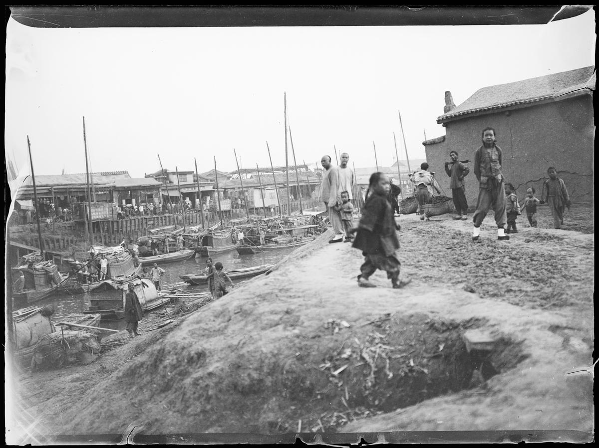 Fra Asia. Voksne og barn ved elvebredden. Båter og arbeidsliv.