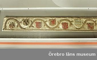 """Altarbrun bestående av en vågformigt löpande stam och 15 vapensköldar, allt sekundärt aplicerat på gulvitt atlassiden. Rankan har med jämna mellanrum stympade grenar. Broderad på lärft i läggsöm, två sorters guldtråd med ziggzaggformad nedfästning med rött silke och därefter applicerad. Fragment av en kontursnodd av guldtråd. Rankan tidigare delad i två ånyo hopfogade delar. Sköldformen av tartchtyp, vanlig kring år 1500. Sköldarna har litet """"öra"""" åt sidan. Broderitekniken typisk för 1400-talets slut.  Från vänster:  1. Okänd släkt: vänd åt höger med svart örn med krona av silvertråd; fältet delat i ett rött och ett blått. Kontursnodd av guldtråd. Mycket nött.  2. Moltke: vända åt höger tre svarta fåglar med röda näbbar och klor; guldtrådsbotten. Svart kontursnodd. 3. Grubbe: tre strålar av silver från vänster mot rött fält. Kontursnodd av guldtråd.  4. Baad af Halland?: i högerprofil rött ox- eller tjurhuvud, fält i guld. Röd kontursnodd. 5. Lunge: tre i y-form placerade liljor; rött fält. Kontursnodd av guldtråd.  6. Dansk Bielke: två blå bjälkar mot fält i guld. Kontursnodd av guldtråd.  7. Svarte Skåning?: diagonalt ställd röd båt med fören uppåt åt höger, teckning i svart, guldfält. Röd kontursnodd.  8. Gyllenstierna: sjuuddig stjärna i guld mot blått fält. Kontursnodd av guldtråd.  9. Laxmand: svan med kropp i silver, huvud av guld samt svart teckning; blått fält. Fragment av guldtrådsnodd.  10. Lange (Munk): tre röda rosor, teckning av snoddar; guldfält. Röd kontursnodd.  11. Danska släkten Brahe: silverstolpe mot svart botten.  12. Fleming: på gyllene fält tre röda bjälkar med åtta gyllene lod. Kontursnodd av guldtråd. 13. Krummedige: träd av silvertråd mot blått fält. Konturtråd av silvertråd.  14. Gyllenstierna: blå sjuuddig stjärna mot fält i guld. Blå kontursnodd.  15. Okänd släkt: röd sparre över svart spaderformat blad; guldfält. Röd kontursnodd.  Broderiet av hög klass, i kvalitet överensstämmande med Albertus arbeten. Det har ursprungligen sannolikt """