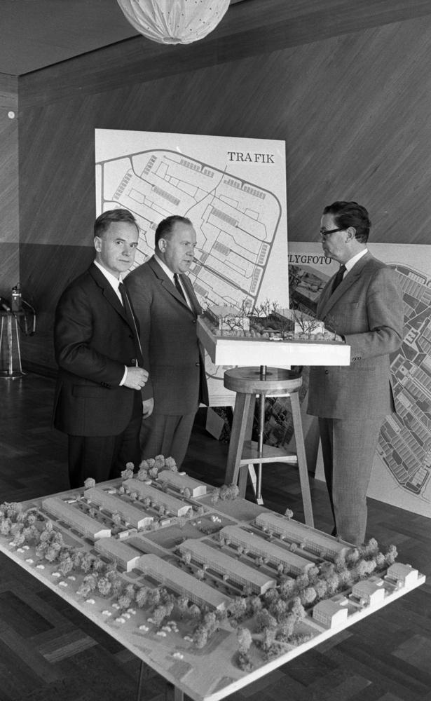 """Trafiktävling, 10 maj 1966Tre herrar klädda i vita skjortor, kostymer samt slipsar står vid en stor skylt med texten """"Trafik"""" på. Vid herrarna står en modell av hus på en hög pall. I förgrunden syns en annan stor husmodell."""