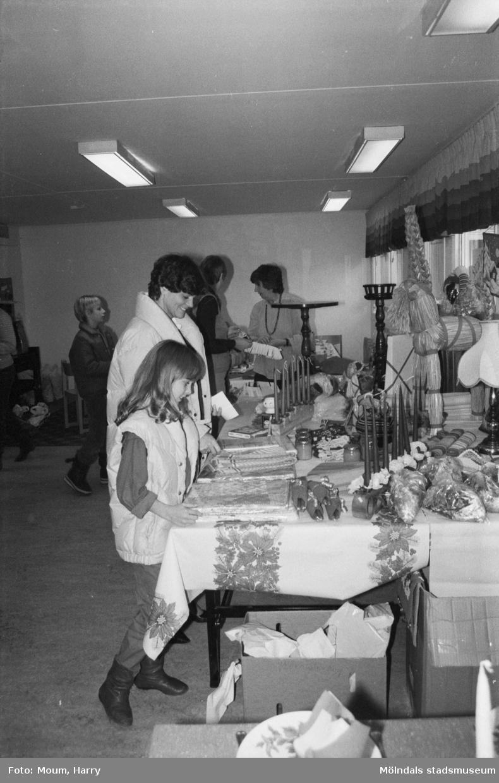 """Lotteri och försäljning i Sankt Johanneskyrkan vid Sagbrovägen i Lindome, år 1983. """"Mona och Pia Mattsson kollar in vinsterna.""""  För mer information om bilden se under tilläggsinformation."""