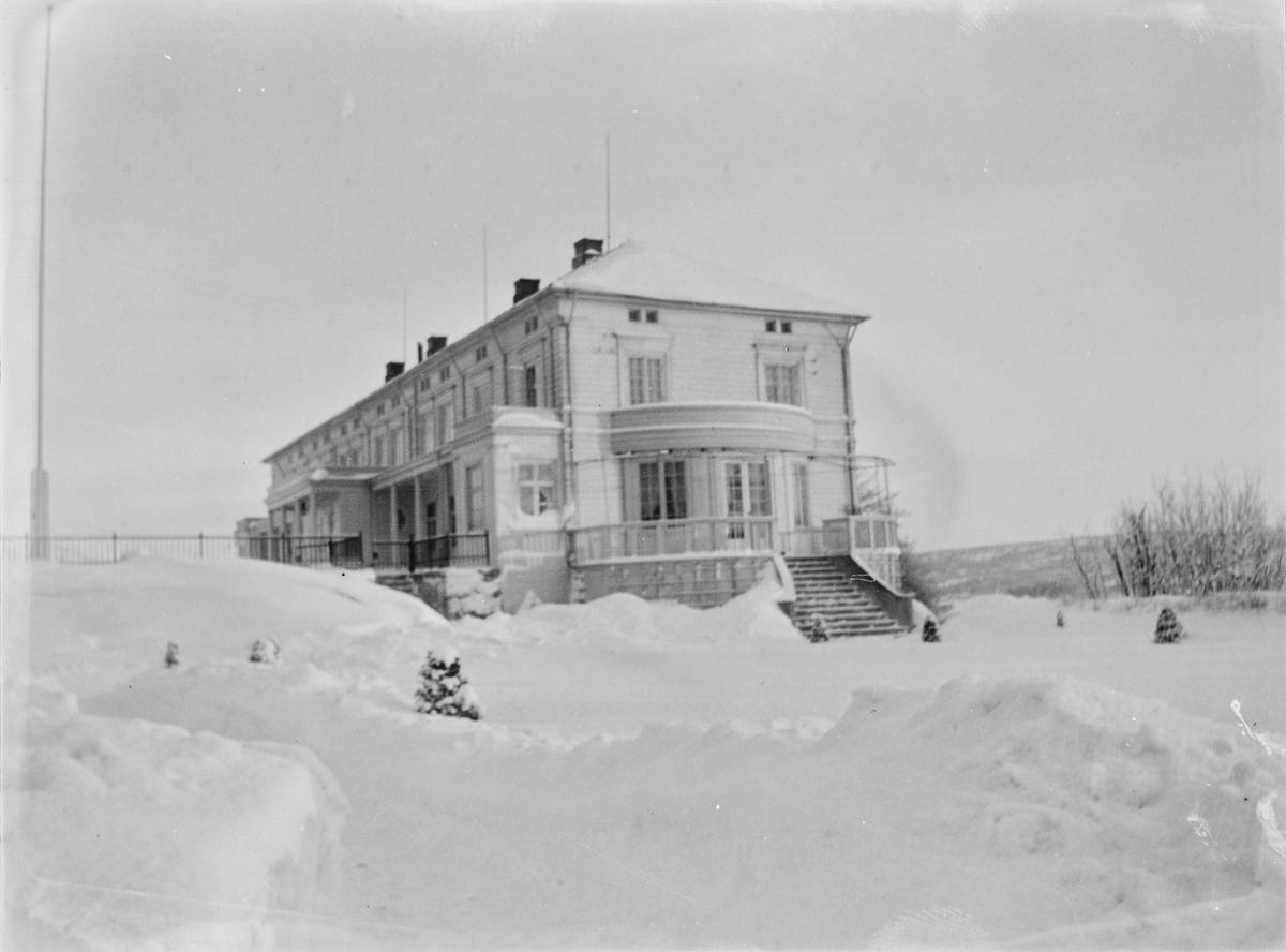 Hageanlegget i vinterskrud. Hovedhuset sett fra siden. En halvsirkelformet veranda samt inngangspartiet med trapper og andre husdetaljer pyntet med snø. Foran sees måkte stier gjennom hagen.
