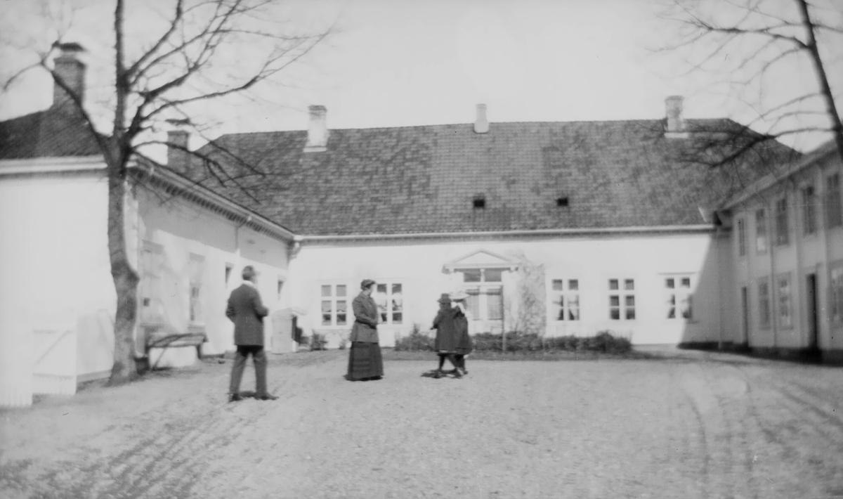En kvinne og en mann samt to barn oppholder seg på gårdsplassen utenfor et hesteskoformet hus.
