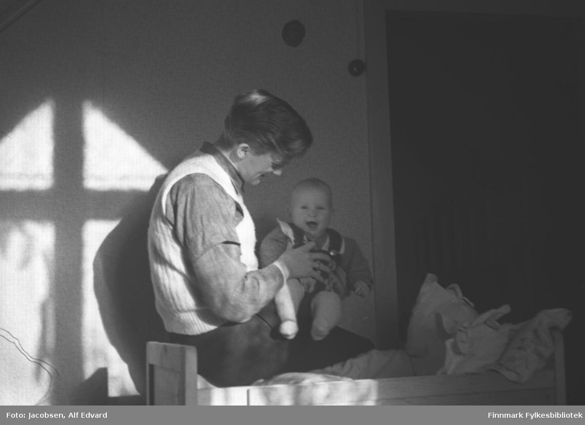 Fridtjof Jacobsen med sønnen Arne på fanget. Fridtjof har en mørk bukse, litt lysere skjorte og en lys/hvit vest på seg. Arne har en lys/hvit strømpebukse, en litt mørkere genser og mørk snekkerbukse på seg. De sitter ved kanten på en trefarget barneseng. En del senge- og barneklær ligger oppi. Veggene er lysmalt og litt til høyre er en døråpning. Dørlisten på ene siden ses på bildet. Ganske langt oppe på veggen, ved siden av dørlisten, er en rund lysbryter. Sola skinner og kaster skygger av vindus-stolpene på veggen bak dem.