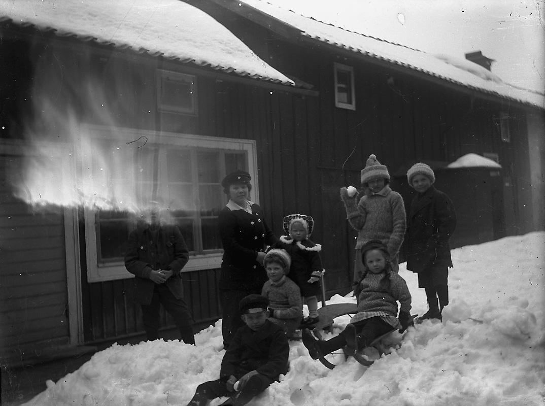 Vintermotiv, en kvinna och sju barn.Troligtvis på gården på Kungsgatan 33, Lindesberg.