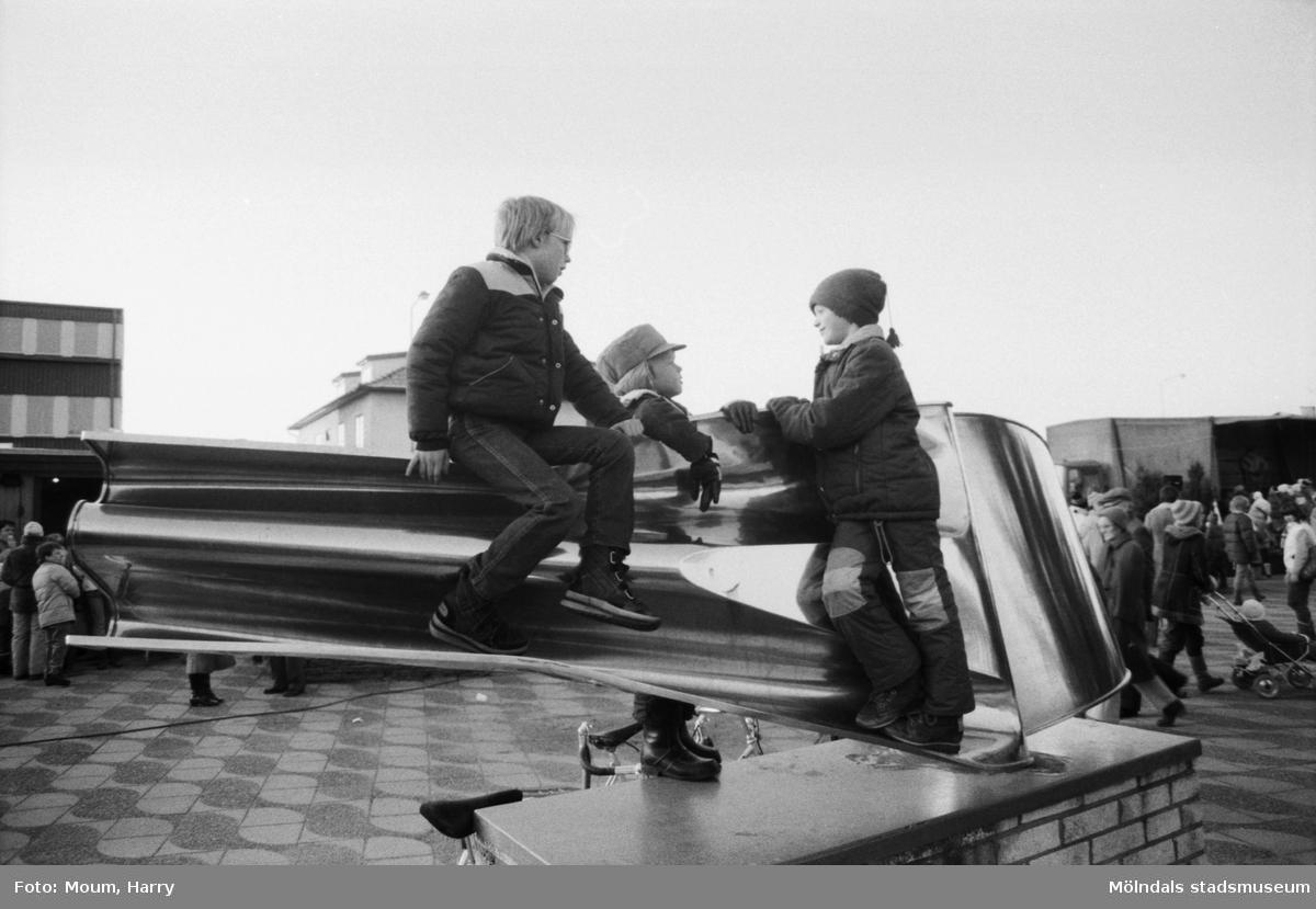 Underhållning i samband med Kållereds lucias kröning i Kållereds centrum, år 1983. Tre pojkar på den skulptur av Gino Scarpa som står på torget.  För mer information om bilden se under tilläggsinformation.
