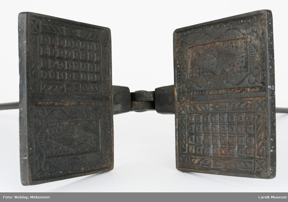 Form: firkantet jern m/plass for to kaker. for- og bakside av bakemønsteret vekselvis på hver plate. smidde armer, holdes sammen av jernbøyle