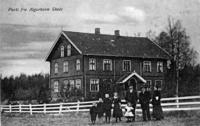 Et historisk bilde av gamle Algarheim skole, med tre voksne og fire barn foran gjerdet.