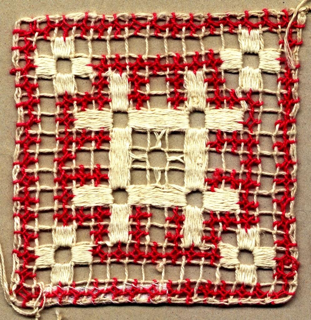 """Kvadratiskt prov av filéknutet nät med trätt mönster, knutet och trätt. Nät av rakställda rutor. Mönster i form av fyra tvärlagda stavar samt rutor i hörnen i tätt trädda stoppstygn i blekt lingarn. Glesare trätt/singlat mönster runt mittmönstret samt som en ram runt om i rosarött bomullsgarn. Knutet nät i blekt 3-trådigt s-tvinnat lingarn. Trädning i samma garn som i nät samt i rosarött 2-trådigt s-tvinnat bomullsgarn. Märkt med en vidhängande prislapp/etikett med texten: """"60/-"""". Jämför med inv.nr 819, 820, 822 och 823."""