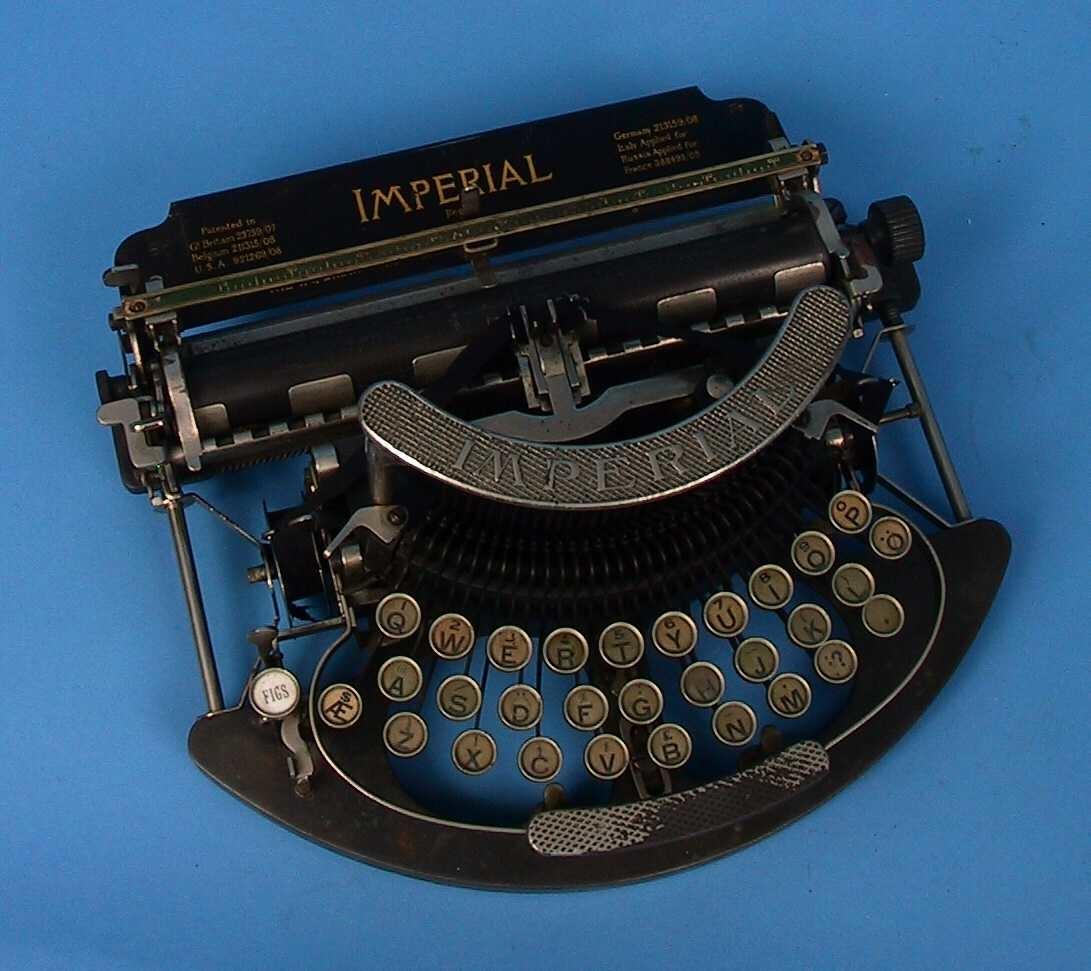 Maskin med åpen konstruksjon, alle bevegelige deler er synlige. Tastatur med bokstaven æ, mens å mangler.