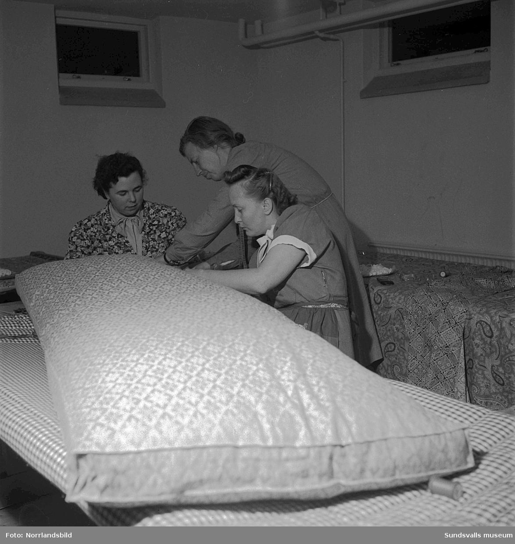 Tre kvinnor som går en kurs i madrasstoppning.