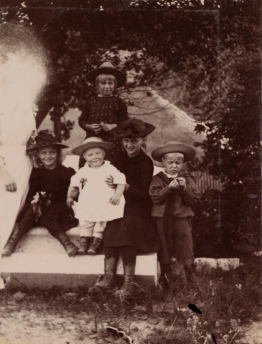 Gruppeportrett av Christensen-barna. Øverst: Eva Christensen, under ra venstre: en uidentifisert eldre jente i hvit kjole, en lysflekk på ansiktet hennes gjør identifisering umulig, Minnie (Emilie), Mogens, Anna og Haaken Christensen.