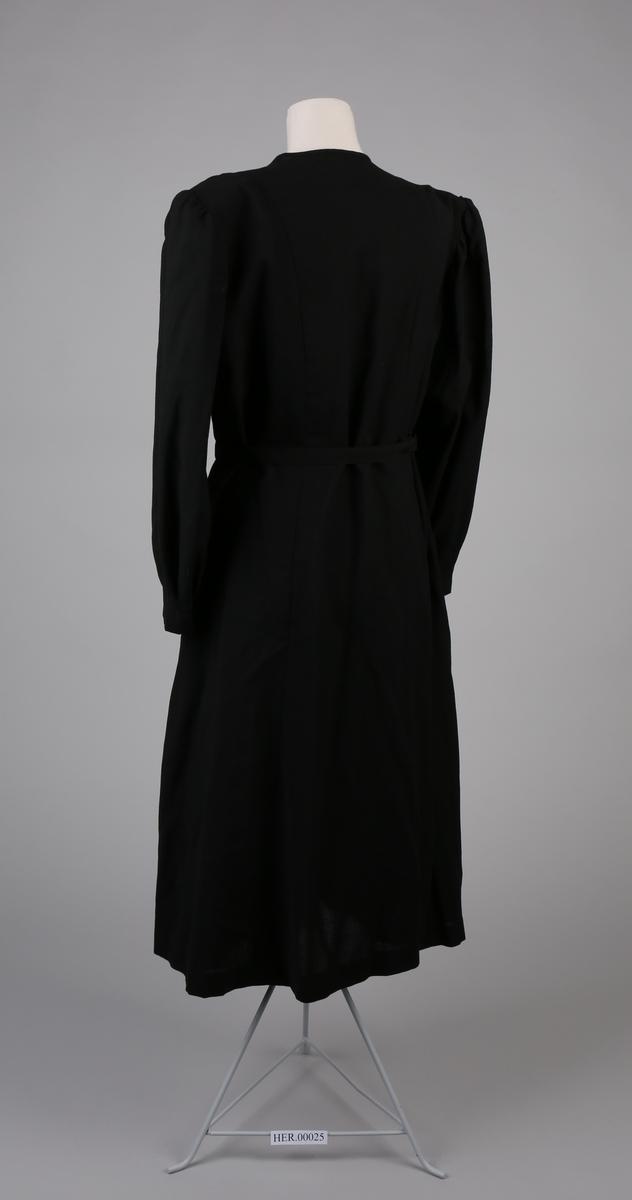 Damekjole med lang arm, skulderputer og belte. Folder og knapper framme
