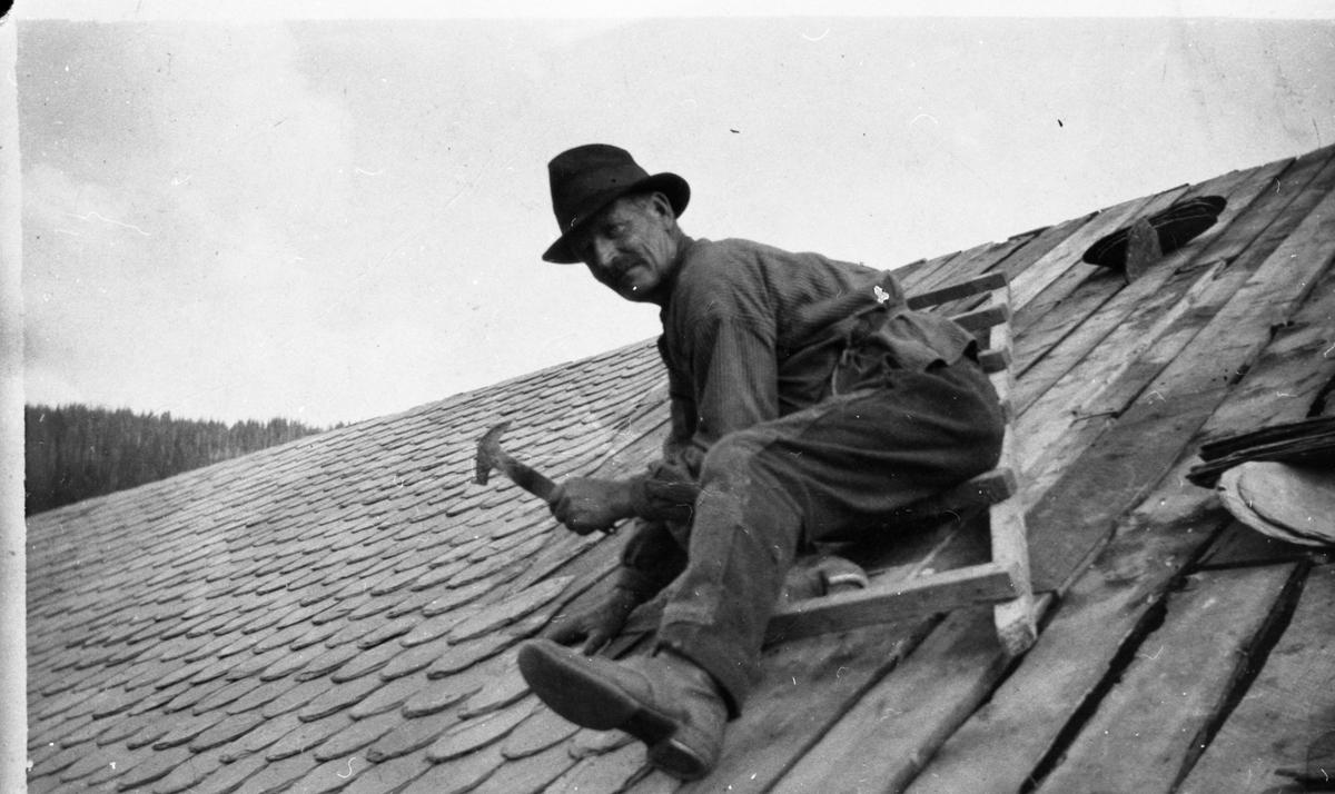 En mann sitter på en stige på et tak, iført hatt og arbeidsklær. Han har en hammer i hånden.
