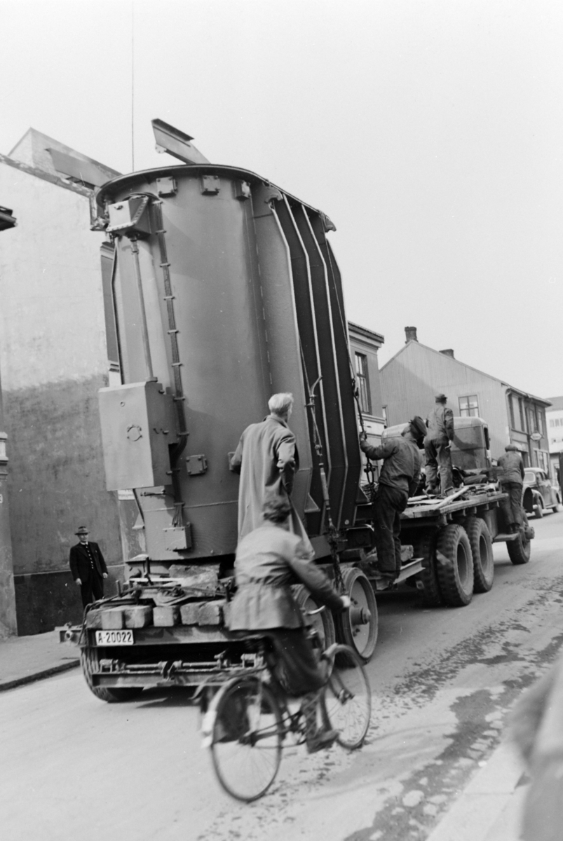 Grønnegata i Hamar. Frakt av 10 MVA transformator til Børstad våren 1949. Transport utført av Fridtjof Kristiansen spedisjon, Oslo. Trekkvogn av merke Mack, type NM, 1943 modell.  Bilens reg-nr er A-44735.Lastebil med folk fra kraftselskapet overvåker transporten. Trekkvogn, tilhenger, A-20022, tungtransport. Hamar Vang og Furnes kommunale kraftselskap.