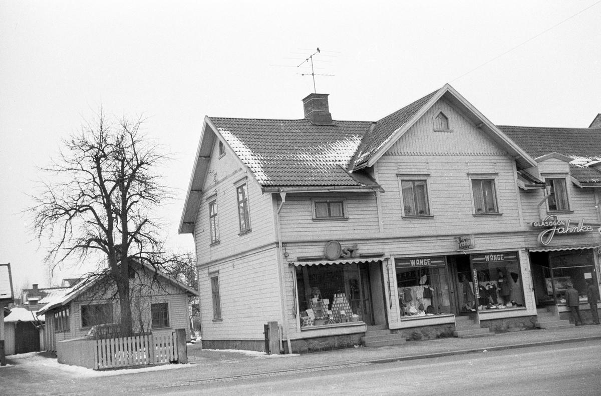 Hus vid Rosenborgsgatan i Huskvarna. En Ost-affär, Wrange barnkläder och Glasögon Jahnke finns i markplan med bostäder på ovanvåningen.
