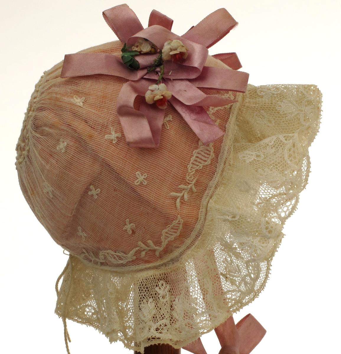 Dåpslue, kysefasong som kvinnekyser fra 1830 årene:  Tyll med små firbladblomster og grenbord langs kanten, rynket til sirkulært felt på issen. under tyllen rosa  silke. Langs kanten to tyllblondekapper over hverandre, over tinningene to sløyfer av lilla silkebånd knyttebånd av samme. Sløyfene har små tøyblomster.
